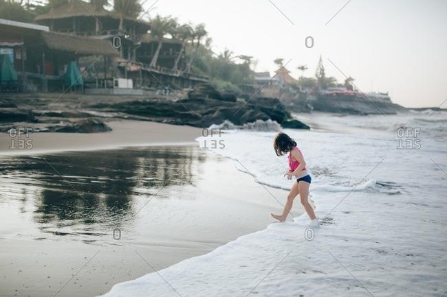 Girl splashing in surf on a beach at sunset