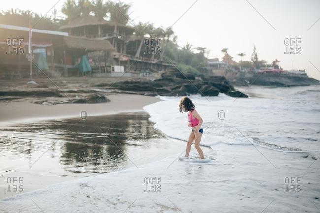 Girl walking through surf on a beach at sunset