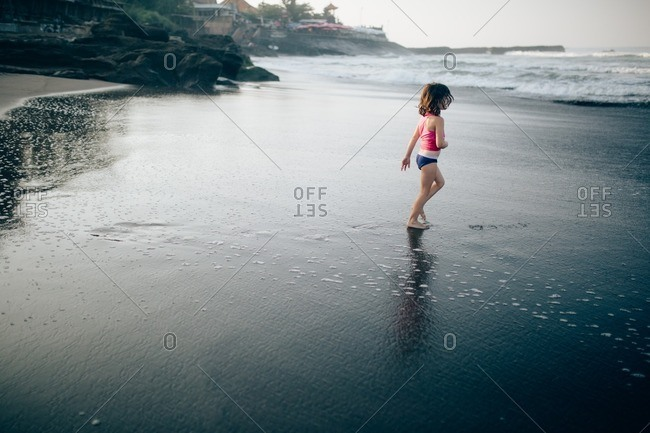 Girl walking on wet sand on a beach at sunset