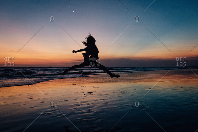 Girl leaping in mid-air on a beach at twilight