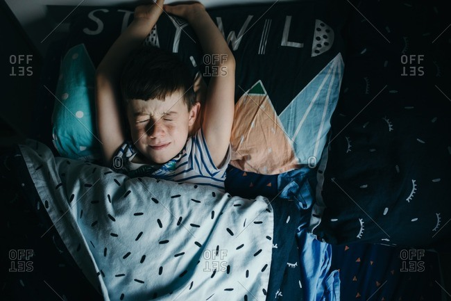 Little boy lying in bed squeezing his eyes shut