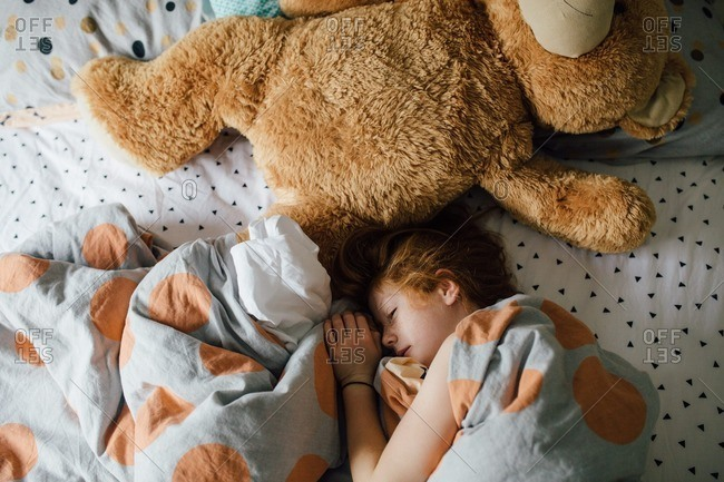 Little girl snuggled under polka dot sheets with an oversized teddy bear