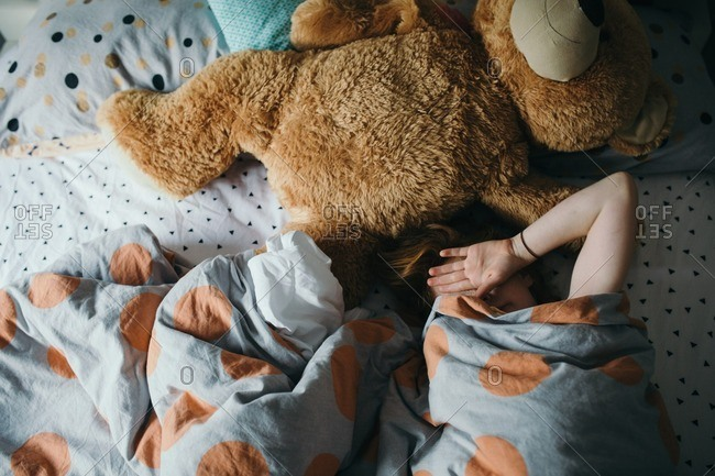 Girl lying in a bed with an oversized teddy bear