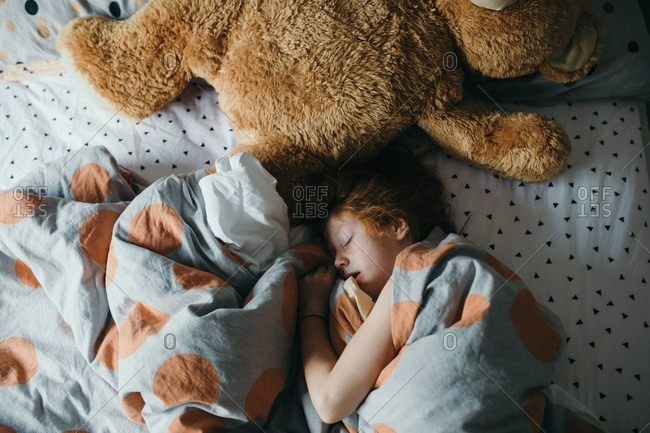 Girl sleeping in a bed with an oversized teddy bear
