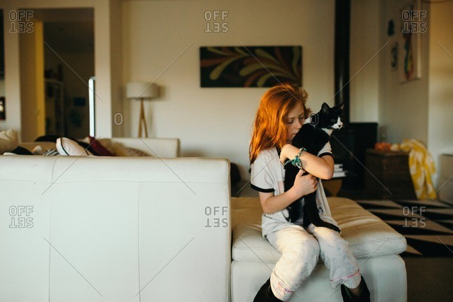 Girl sitting on a sofa snuggling her cat