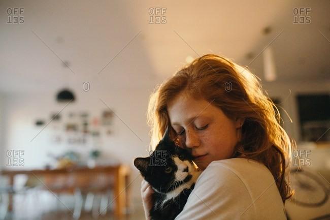Little girl snuggling her cat