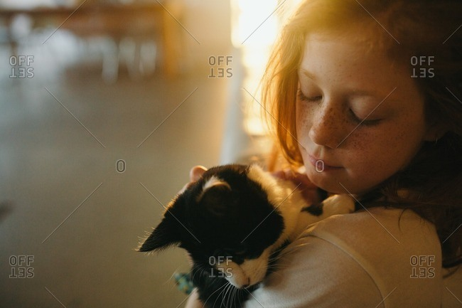 Little girl holding her cat in her arms