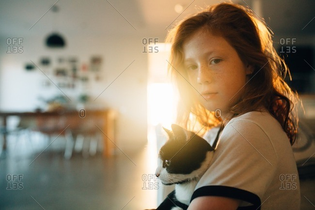 Little girl sitting with her cat in her lap