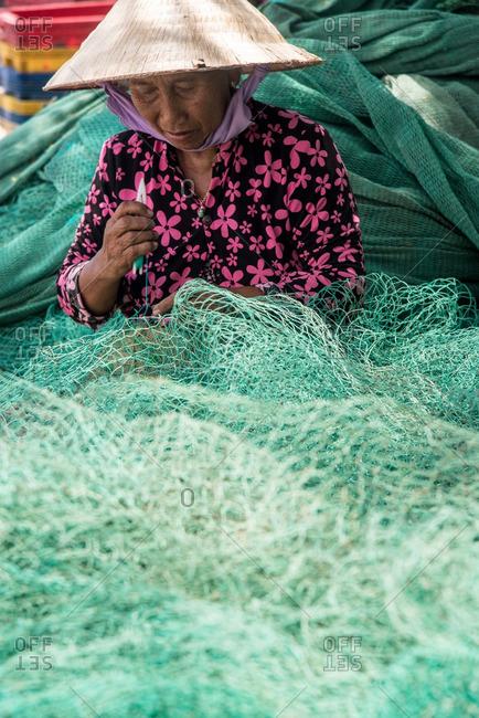 Nha Trang, Vietnam - September 6, 2016: Vietnamese woman wearing conical hat stitching fishing net