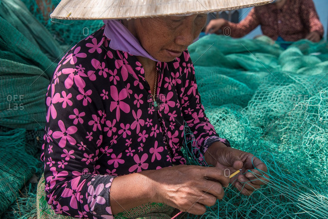 Nha Trang, Vietnam - September 6, 2016: Close up of Vietnamese woman stitching fishing net