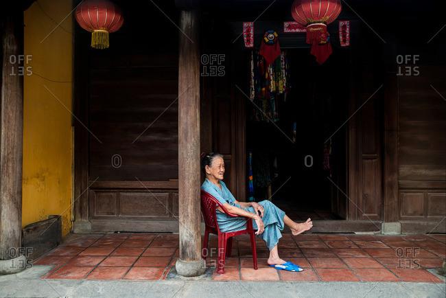 Hoi An, Vietnam - September 11, 2016: Elderly Vietnamese woman sitting in front of her shop in Hoi An