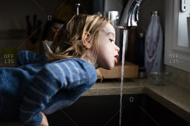 Girl drinking water from faucet