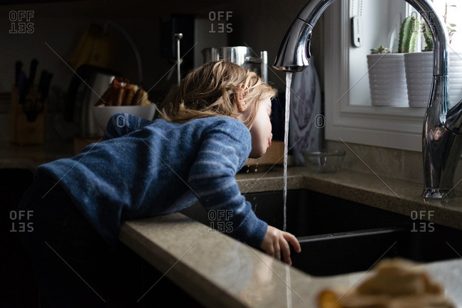 Girl drinking water from a faucet