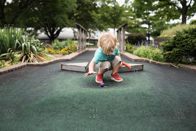 Toddler boy watching ball approach the hole on a miniature golf course