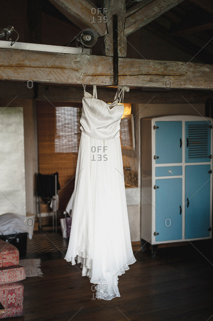 Wedding dress hanging on a wooden beam in historic house