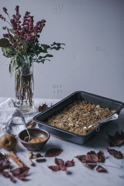 Pear and cinnamon baked oatmeal in a baking pan and coconut sugar in a bowl on white marble table