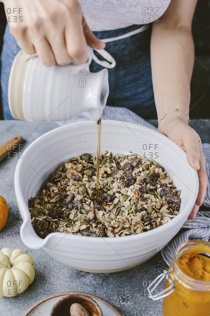 Woman pouring maple syrup into a nut mixture to make pumpkin cranberry nut loaf