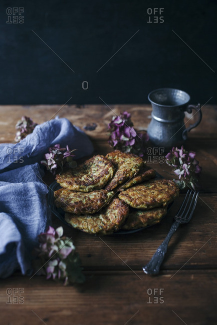 Close up of zucchini, carrot and cheese fritters on a plate on rustic wooden table