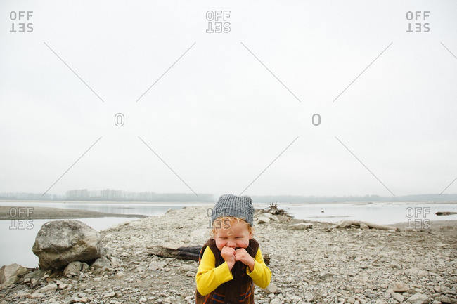 Giggling little boy on rocky lake shore
