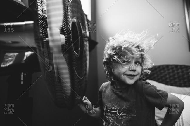 Boy standing by blowing fan