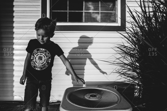 Boy standing by air conditioning unit