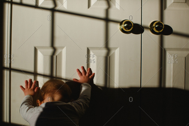 Boy pushing against door in shadow