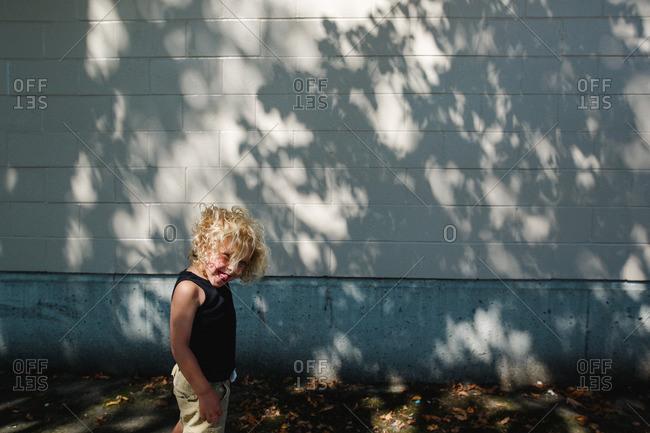 Gleeful blonde boy by shadowy building