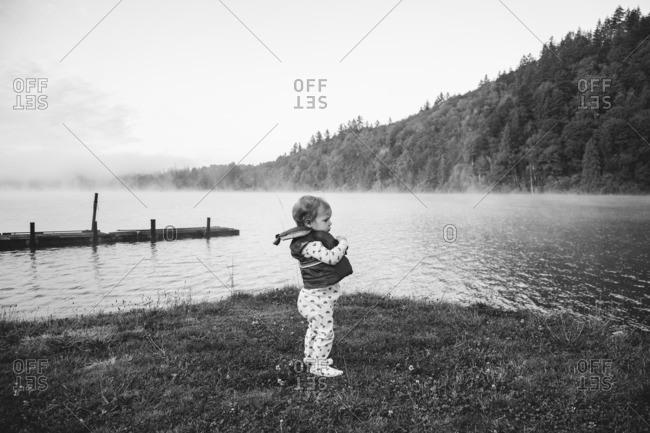 Toddler girl on the shore of misty lake