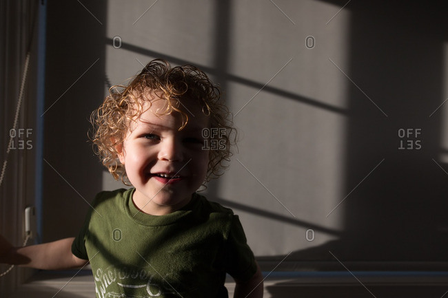 Curly haired boy grinning in sunlight