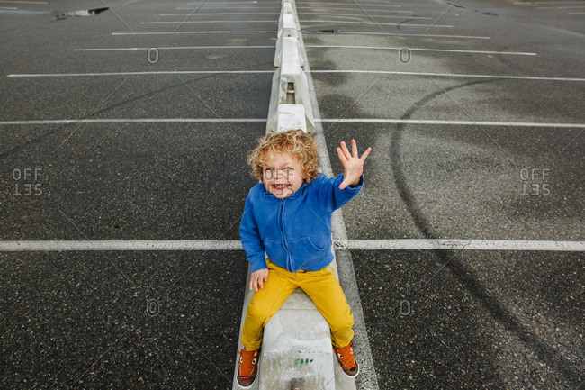 Grinning boy on parking lot ledge