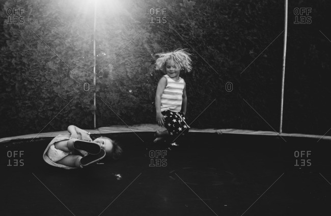 Two kids bouncing around on trampoline