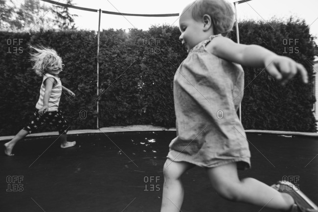 Two kids bouncing around a trampoline