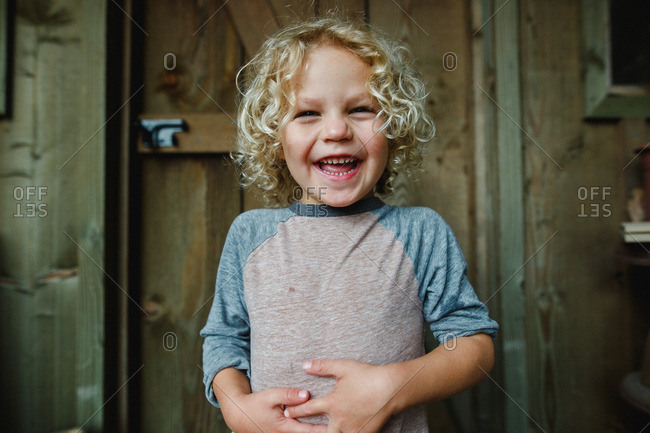 Delighted boy with curly blonde hair