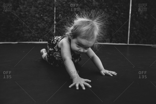Toddler with frizzy hair on trampoline