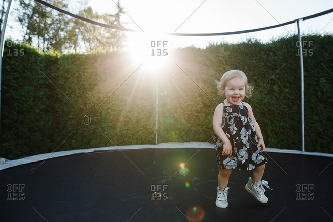 Grinning toddler girl on trampoline