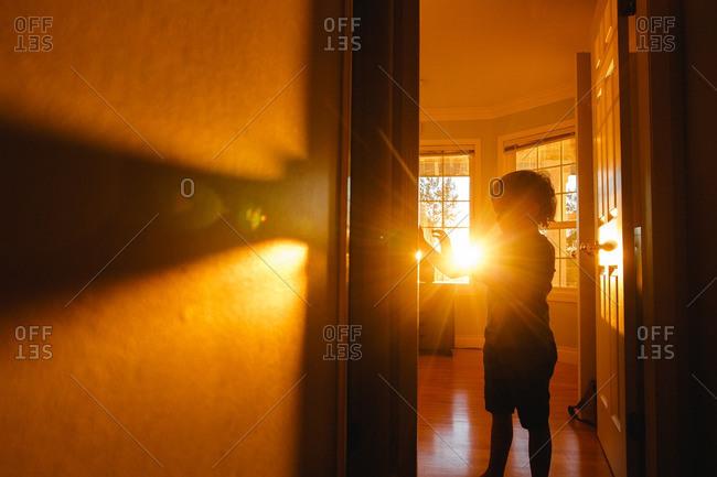 Boy in a doorway backlit by sunlight