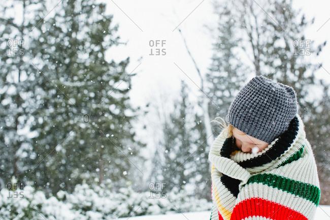 Boy wrapping in blanket in winter