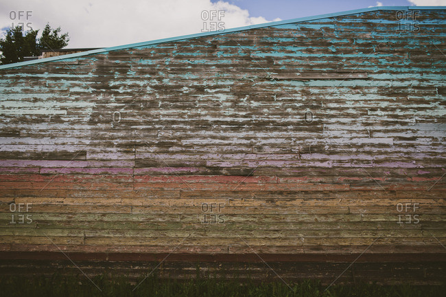 Exterior wall of a building with peeling paint in a rainbow spectrum