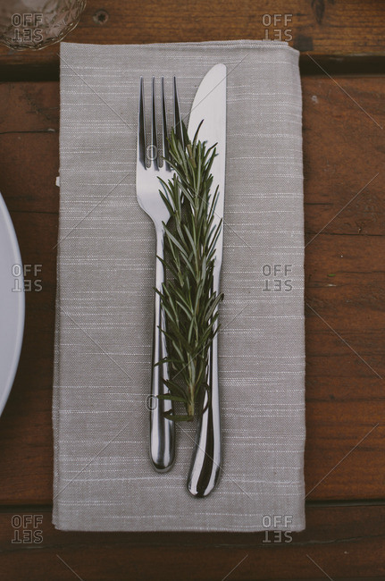 Silverware place setting with a rosemary sprig