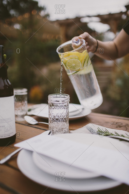 Person pouring water tableside