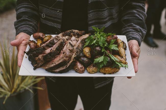 Person serving prime rib and potato dinner
