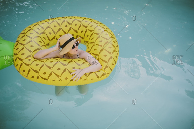 Woman floating on a pineapple float