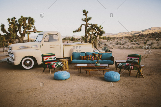 Joshua Tree, CA, USA - July 1, 2016: Mid western style living room staged in the desert in front of a vintage truck