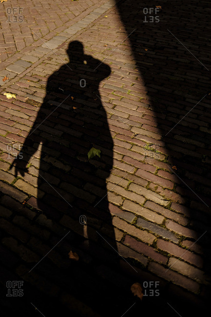 Shadow of a human on a brick walkway