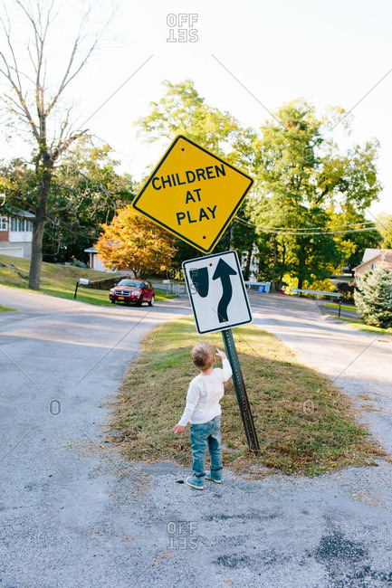 """Boy standing by sign that says """"Children at play"""""""