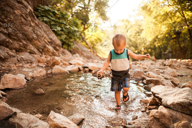 Toddler boy splashing in a river