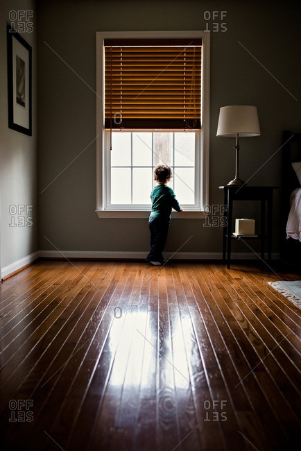 Little boy alone by window