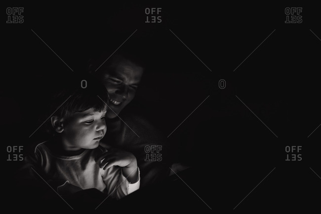 Boy and dad in glow from tablet
