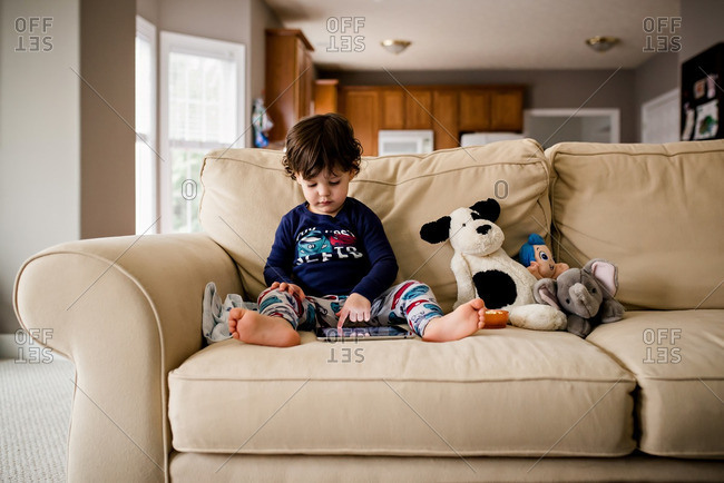 Boy using tablet by dolls