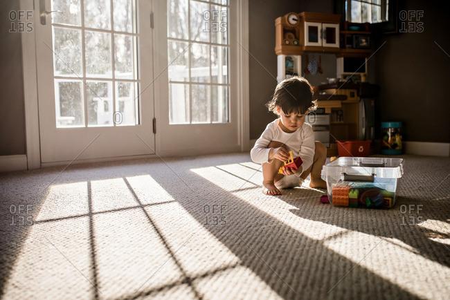 Boy putting away his block toys